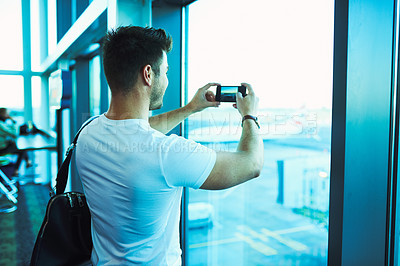 Buy stock photo Shot of a young man taking pictures of the view from an airport window