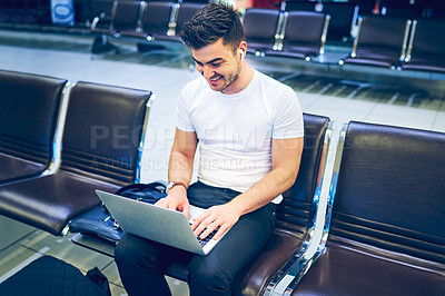 Buy stock photo Shot of a young man using a laptop in an airport