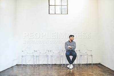 Buy stock photo Shot of a young man sitting on a chair against a white wall