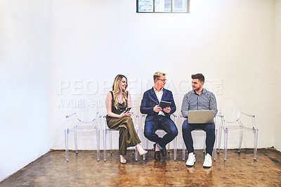 Buy stock photo Shot of a group of businesspeople having a discussion and using digital devices while sitting in line