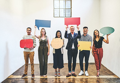 Buy stock photo Portrait of a group of businesspeople holding colourful speech bubbles in an office
