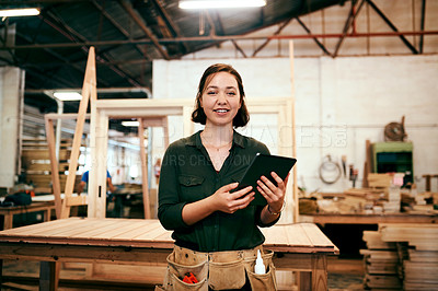 Buy stock photo Shot of a female carpenter using a digital tablet in her workshop