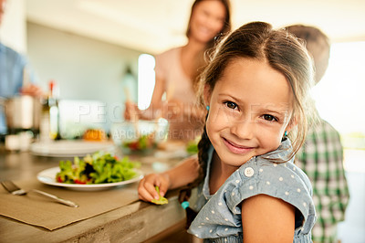 Buy stock photo Cropped portrait of a happy young girl sitting at the table and about to eat lunch with her family