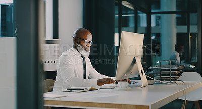 Buy stock photo Shot of a mature businessman working on a computer inside his office at night