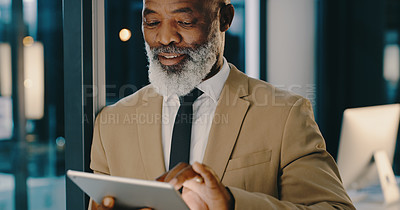 Buy stock photo Shot of a mature businessman using a digital tablet inside his office