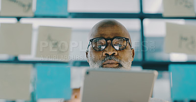 Buy stock photo Shot of a mature businessman using a digital tablet while brainstorming ideas on a glass board inside his office