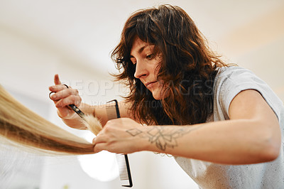 Buy stock photo Cropped shot of an attractive young hairdresser standing and cutting a client's hair in her salon