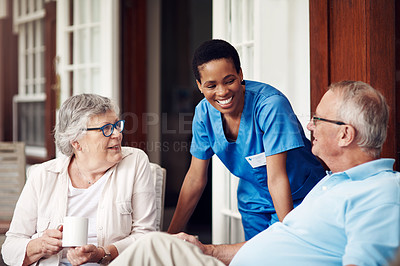 Buy stock photo Cropped shot of an attractive young nurse bonding with her senior patients during a day out on the veranda