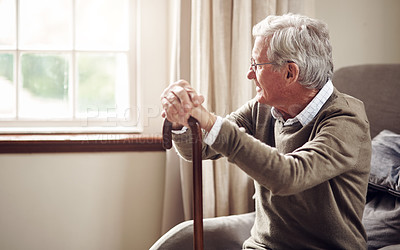 Buy stock photo Shot of a senior man looking thoughtfully out of a window at home