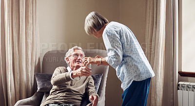 Buy stock photo Shot of a senior woman giving her husband medication with a glass of water