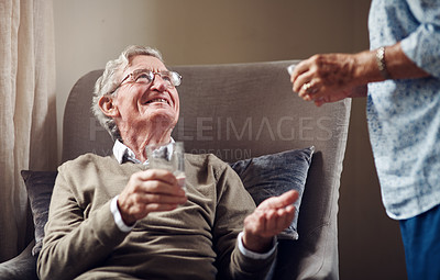 Buy stock photo Shot of a woman giving her senior husband medication with a glass of water