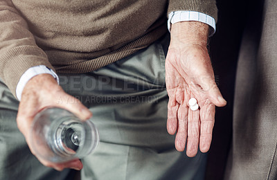 Buy stock photo Cropped shot of a senior man taking his medication with a glass of water
