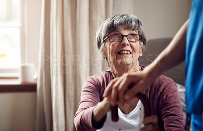 Buy stock photo Shot of a nurse caring for a senior woman with a walking stick at home