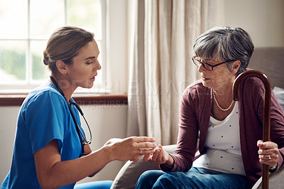 Buy stock photo Shot of a nurse giving a senior woman her medication at home