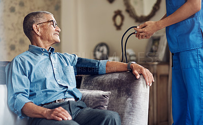 Buy stock photo Shot of a senior man getting his blood pressure measured during a checkup with a nurse at home
