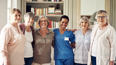 Buy stock photo Cropped portrait of an attractive young nurse standing with her senior patients in the living room of a nursing home