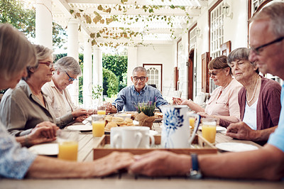 Buy stock photo Cropped shot of a group of senior citizens sitting together and holding hands to pray before enjoying their tea party