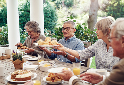 Buy stock photo Cropped shot of a group of senior citizens sitting together and enjoying a tea party outdoors