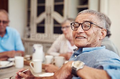 Buy stock photo Cropped portrait of a happy senior man sitting and enjoying a tea party with his friends outdoors