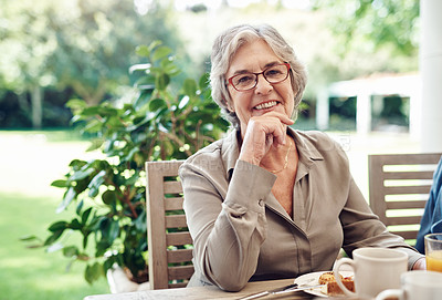 Buy stock photo Cropped portrait of a happy senior woman sitting with her hand on her chin during a tea party outdoors