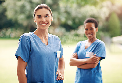 Buy stock photo Portrait of two confident young nurses standing outside in the garden of a retirement home