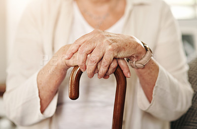 Buy stock photo Cropped shot of a senior woman using a walking stick at home