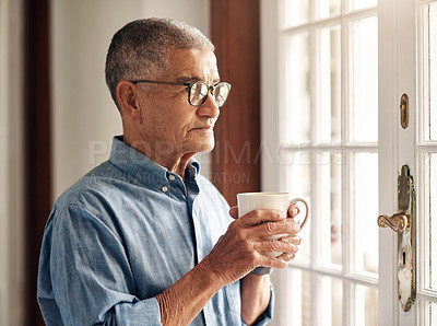 Buy stock photo Shot of a senior man having coffee and looking thoughtfully out of a window