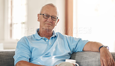 Buy stock photo Shot of a senior man having a coffee break on the sofa at home