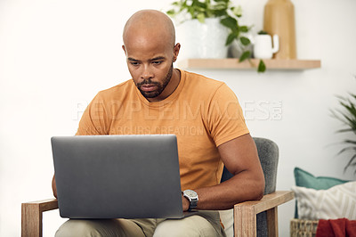 Buy stock photo Shot of a young man using his laptop while sitting on the sofa at home