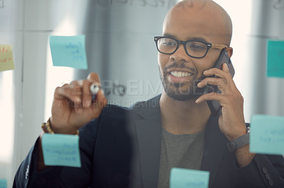 Buy stock photo Shot of a young businessman talking on the phone while brainstorming on a glass wall