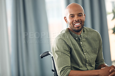 Buy stock photo Cropped shot of a young man sitting in his wheelchair at home