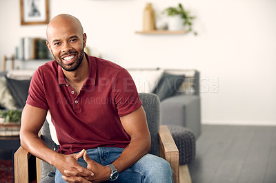 Buy stock photo Cropped shot of a handsome young man sitting at home