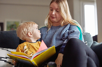 Buy stock photo Cropped shot of an adorable little boy reading a book while sitting with his mother at home