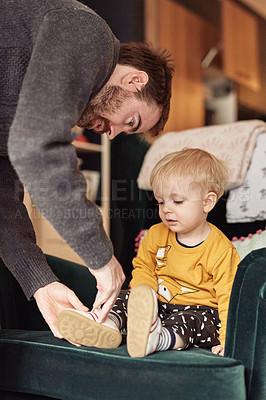 Buy stock photo Cropped shot of an affectionate young father helping his little son put on shoes at home