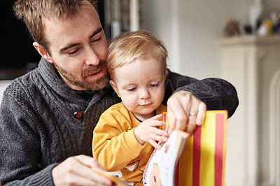 Buy stock photo Cropped shot of an adorable little boy reading a book while sitting with his father at home
