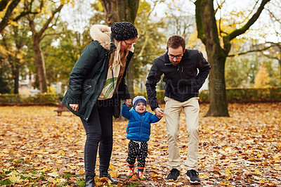 Buy stock photo Full length shot of an affectionate young couple walking through a park with their little son in autumn
