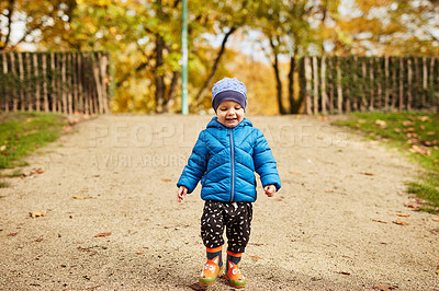 Buy stock photo Full length shot of an adorable little boy walking though a park alone in autumn