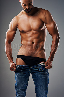 Buy stock photo Rearview shot of a handsome young man undressing against a grey background