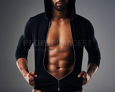 Buy stock photo Cropped shot of an unrecognizable muscular young man posing in a zipped down hoodie against a grey background