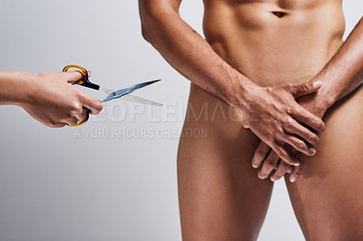Buy stock photo Shot of an unrecognizable woman holding a pair of scissors next to naked man against a grey a background