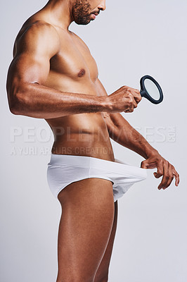 Buy stock photo Cropped shot of an unrecognizable man in underwear checking his pubic area against a grey background