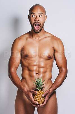 Buy stock photo Portrait of a naked man posing with a pineapple covering his genital area against a grey background