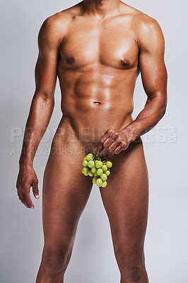 Buy stock photo Shot of an unrecognizable naked man posing with a bunch of grapes covering his genital area against a grey background