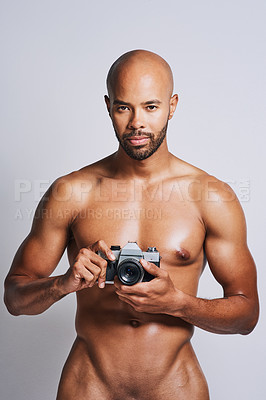Buy stock photo Portrait of a naked young man taking pictures with a camera against a grey background