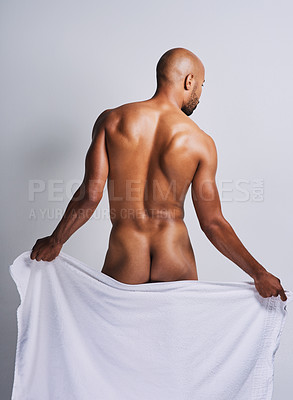 Buy stock photo Rearview shot of a naked young man wiping himself off with towel against a grey background