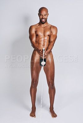 Buy stock photo Full length shot handsome young man posing nude and popping a bottle of champagne against a grey background