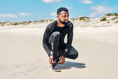 Buy stock photo Shot of a carefree young man tying his shoe laces before starting with training exercises outside next to a beach during the day