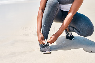 Buy stock photo Cropped shot of an unrecognizable woman tying her shoe laces before starting with training exercises outside next to a beach during the day