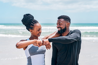 Buy stock photo Cropped shot of a cheerful young couple locking fists while standing on a beach together outside during the day