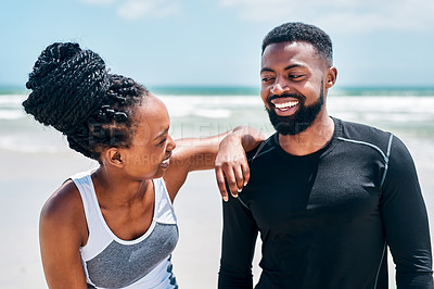 Buy stock photo Cropped shot of a confident young couple standing together while looking into each other's eyes on a beach outside during the day